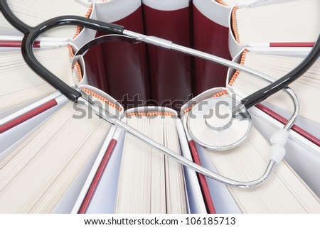Set of encyclopedias, books and stethoscope closeup. - stock photo