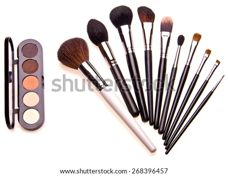 Set of essential professional make-up brushes and eye shadows are isolated with shadows on white background. Overhead view. Black and white kit. - stock photo