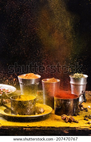 Set of exploding spices pepper, turmeric, anise, coriander in vintage metal cups over black background - stock photo