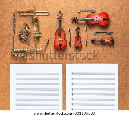Set of five golden brass wind and four string musical orchestra instruments: saxophone, trumpet, french horn, trombone, violin, cello, contrabass, viola and sheet music lying near it. Music concept. - stock photo
