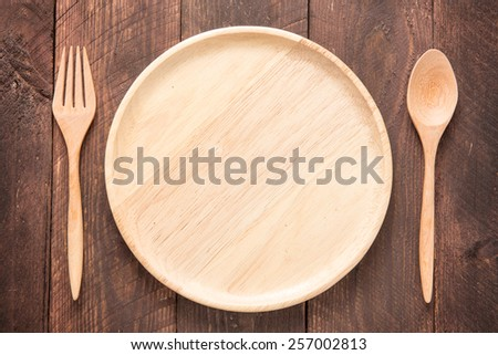 Set of fork,spoon and dish wood on wooden table. - stock photo