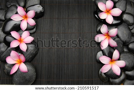 Set of frangipani with zen stones on mat - stock photo