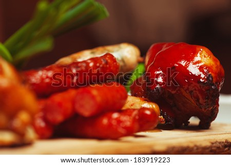 Set of fried meat and small meat sausages served with scallion on wooden cutting board. German kitchen. Close up. Indoor shot - stock photo