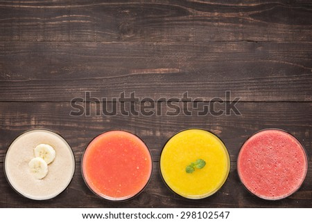Set of fruit smoothie and juice in glasses on wooden background with a lot of copy space for your text or editing. - stock photo