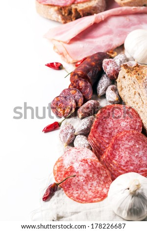 Set of ham and salami sausages served with fresh bread, garlic and red hot chili peppers over white - stock photo
