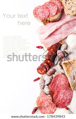 Set of ham and salami sausages served with fresh bread, garlic and red hot chili peppers over white with sample text - stock photo