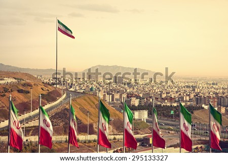 Set of Iran flags in Front of Tehran Skyline and one large flag in the background at sunset with orange warm tone. - stock photo