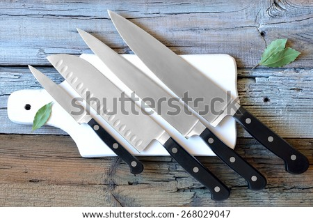 Set of kitchen knives on a board, top view - stock photo