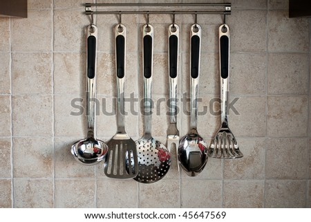 Set of kitchen utensil hanging on the tiled wall - stock photo