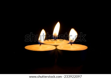 Set of lighting candles in a row on dark background - stock photo