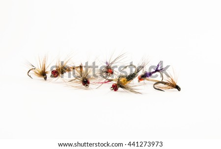 Set of lures flies for fly fishing on a uniform white background close-up front view. Elements of fishing equipment or tackle for fly fishing - stock photo
