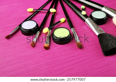 Set of makeup brushes on pink wooden table background - stock photo