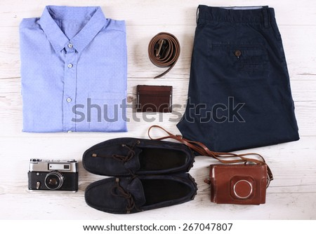 Set of male casual clothing, and retro photo camera on wooden background - stock photo