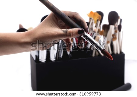Set of many professional make-up brushes for eyeshadow powder and facial foundation for visagistes in black plastic box and human hand holding one brush on white background, horizontal picture - stock photo