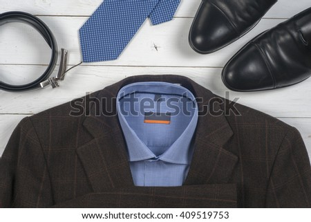 set of men's clothing and shoes on wooden background. Men accessories. Black elegant accessories pieces isolated on white wooden table. Top view. Copy space for text. - stock photo