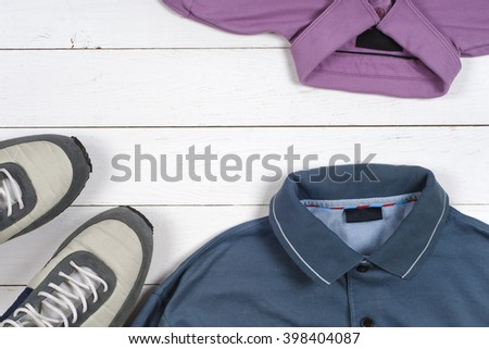 set of men's clothing and shoes on wooden background. Sports T-shirt and sneakers in bright colors. Top view - stock photo
