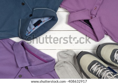 set of men's clothing and shoes on wooden background. Sports T-shirt and sneakers in bright colors. Top view. Copy space for text. - stock photo