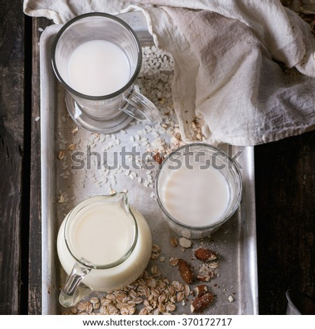 Set of non-dairy milk (rice milk, almond milk and oat milk) in glass cups on old aluminum tray with rice grains, oat flakes and almond over old wooden table. Dark rustic style. Top view. Square image - stock photo
