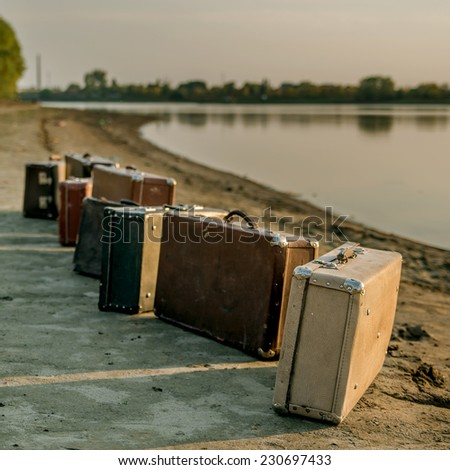 Set of old suitcases on the riverside. Toned photograph. - stock photo