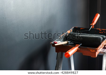 Set of paint tools, paint brushes, paint roller in paint tray for painting, Grey wall background, Copy space. - stock photo