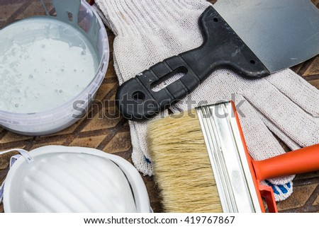 Set of paint tools: paint, gloves, brush, spatula and breath mask on rusty metal plate - stock photo