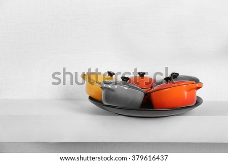 Set of pans on shelf against white wall background - stock photo