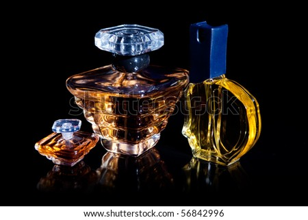 Set of perfume bottles with reflection on black background - stock photo