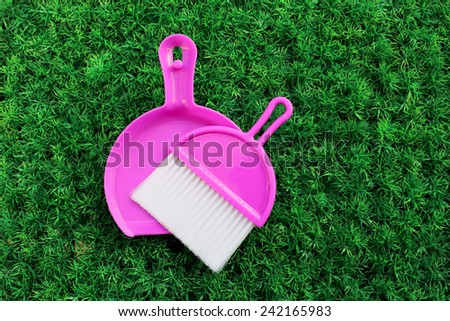 set of pink cleaning dust on artificial turf - stock photo