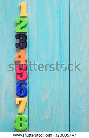 Set of plastic numbers on wooden background with copy-space - stock photo