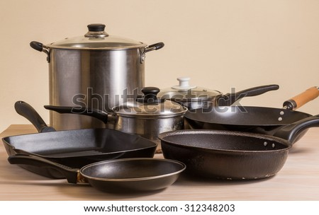 Set of pots and pans on wooden table - stock photo
