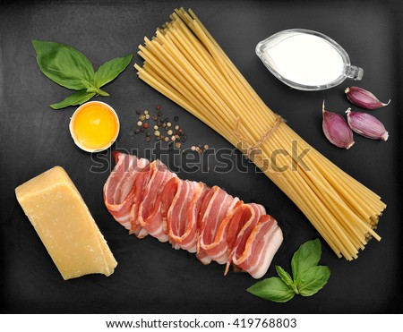 set of products for pasta Carbonara - spaghetti, bacon, cream, Parmesan cheese, Basil, egg, garlic, spices - on black background, top view - stock photo