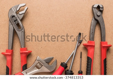 Set of pump plier, plier, screwdrivers and wrenches. Tools over a wood panel. Top view with copy space. - stock photo