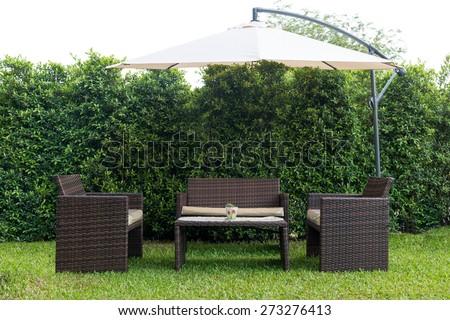 Set of rattan garden furniture under a big garden umbrella,clipping path - stock photo