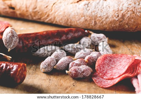 Set of salami served with fresh bread on old wooden cutting board. See series. - stock photo