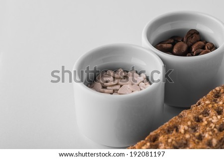 Set of saucers full coffee beans and candy with crispbread on white background - stock photo