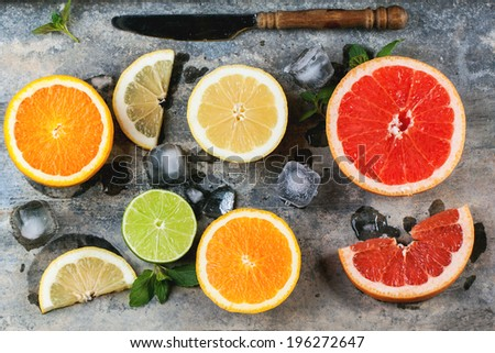 Set of sliced citrus fruits lemon, lime, orange, grapefruit with mint, ice and vintage knife over metal background. Top view. - stock photo