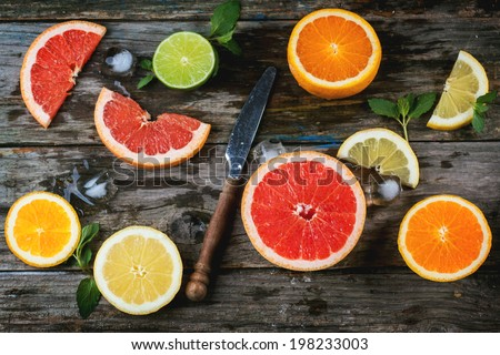 Set of sliced citrus fruits lemon, lime, orange, grapefruit with mint, ice and vintage knife over wooden background. Top view. - stock photo