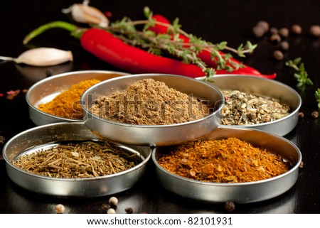 Set of spices, fresh thyme and red hot chili peppers on black table - stock photo