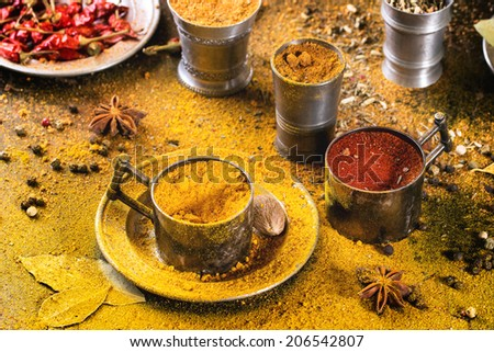 Set of spices pepper, turmeric, anise, coriander in vintage metal cups over yellow curry powder - stock photo