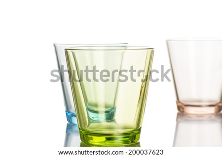 Set of stylish colorful whiskey tumblers tinted green, blue and brown on a reflective white background with focus to the green glass in the foreground - stock photo