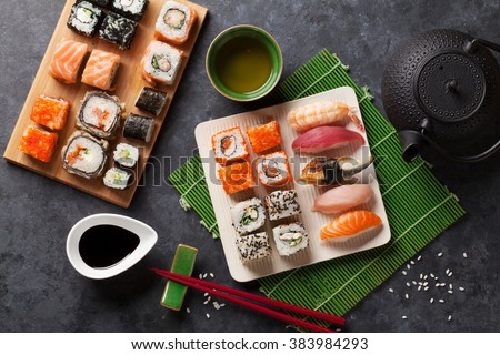 Set of sushi and maki roll and green tea on stone table. Top view - stock photo