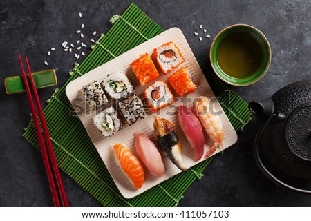 Set of sushi, maki and green tea on stone table. Top view - stock photo