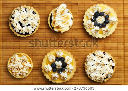 Set of tartlets with lemon curd, berry confiture and meringue top view - stock photo