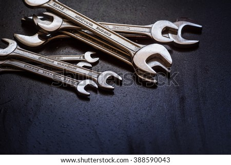 Set of the stainless steel wrench on dark background with space for text - stock photo