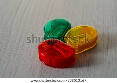 set of three bright multicolored pencil sharpeners on the wooden table - stock photo