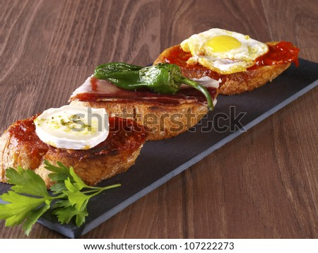 Set of three different montaditos. Montadito is an appetizer or snack (Spanish Tapa) made with a slice of bread with some other food on it. - stock photo