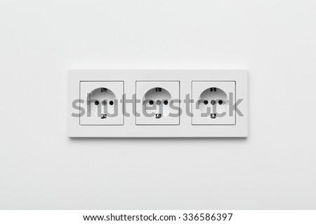 Set of three sockets on the white wall - stock photo
