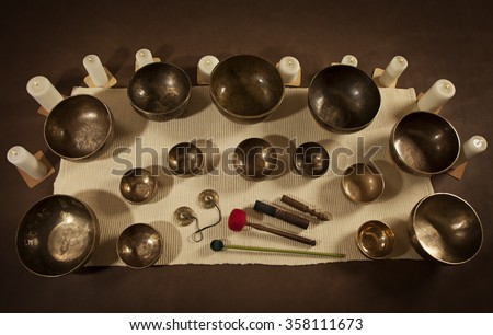 Set of Tibetan singing bowls and bells with burning candles - stock photo
