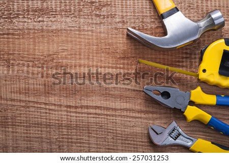 set of tools hammer tapeline pliers wrench on vintage wooden board with copysapce construction concept  - stock photo