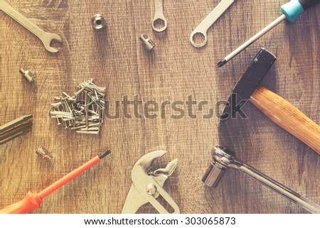 Set of tools on a wooden table. Image cross processed for grunge look. - stock photo
